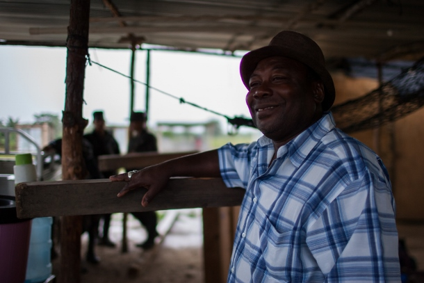 A resident of Vallecito accompany's singers as they preform traditional Garifuna songs. (WNV/Jeff Abbott)