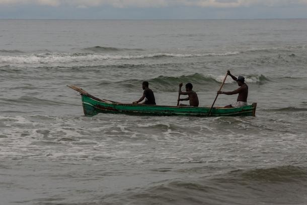 Three Garifuna men set off to fish from the beach in the community of Sambo Creek. (WNV/Jeff Abbott)