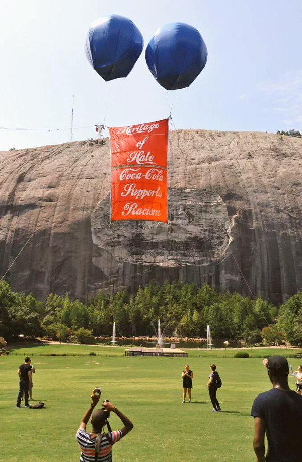 Rise Up members unveiled a banner at Stone Mountain on Sunday, calling out Coca-Cola for sponsoring racism and white supremacy. (Facebook / Rise Up)
