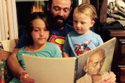 Frida Berrigan's husband Patrick Sheehan reads to their children Rosena (left) and Seamus (right). (WNV / Frida Berrigan)