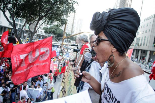 Banderas de la Coalición del Sindicato de los Trabajadores o CUT ondean en la multitud cuando el portavoz de la facción de jóvenes del Movimiento de los Sin Tierra, Levante Popular, habla en la marcha en contra de la destitución en Río de Janeiro el 20 de agosto (Mídia NINJA)