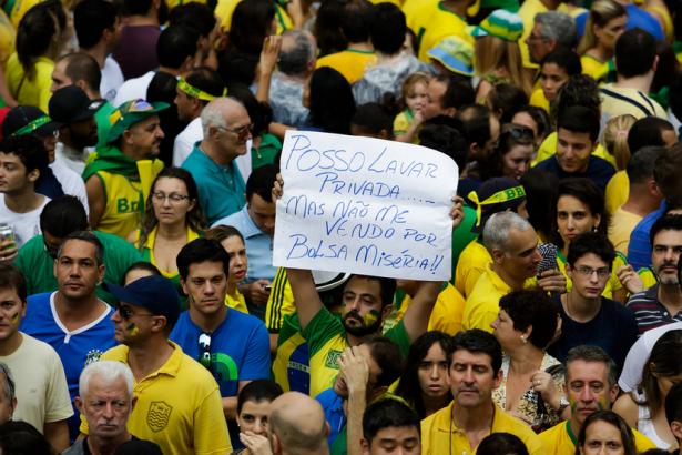 """En una marcha a favor de la destitución, en São Paulo, el 15 de marzo, un hombre sostiene un cartel que dice: """"Prefiero limpiar aseos que venderme a mí mismo por un mísero subsidio"""" refiriéndose a la Bolsa Familia, programa de renta básica del gobierno. (Jornalistas Livres / Alice Vergueiro)"""