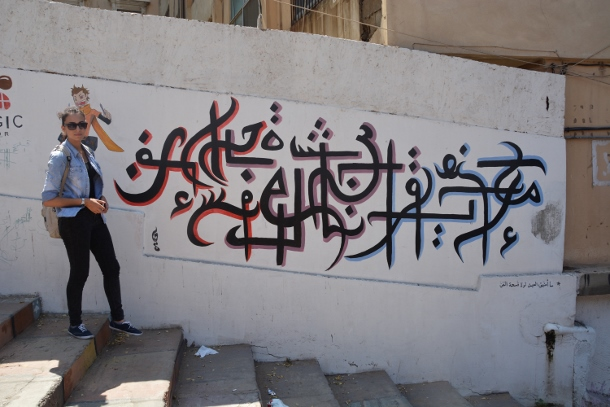 Hayat Chaaban stands next to one of her murals in Tripoli. (WNV/