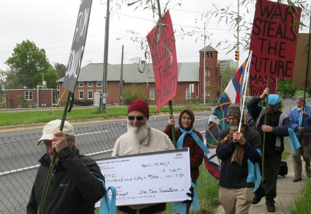 Peter Smith carries a check representing redirected war taxes in a demonstration accompanying the NWTRCC national gathering in Asheville, North Carolina, in May 2013. (WNV/Ruth Benn)
