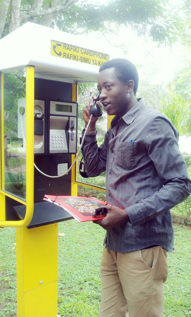 Oyoo posing at a payphone, which no longer work in East Africa. (WNV / Phil Wilmot)