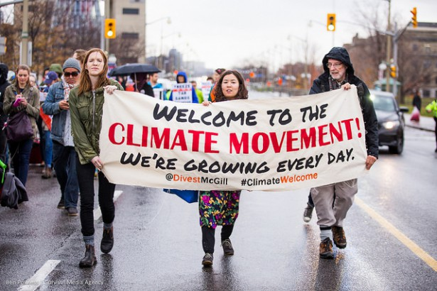 Three people march in the streets as part of an 80 person acton to give the new Prime Minister, Justin Trudeau, a Climate Welcome. (Survival Media Agency / Ben Powless)