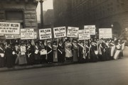 Women suffrage activists wearing suffrage sashes demonstrating with signs at city street corner in 1916. (Wikimedia)