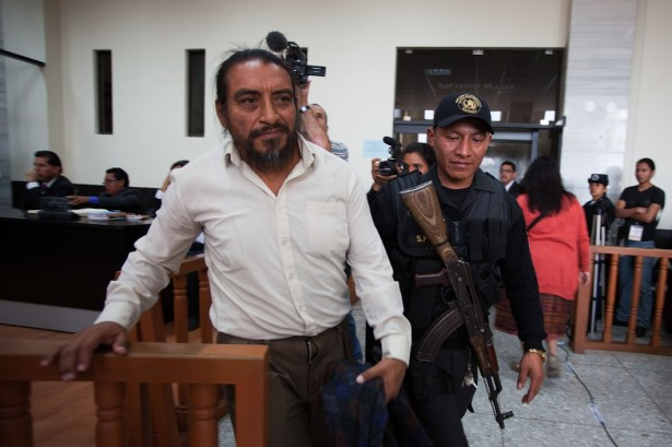 Rigoberto Juarez is escorted back to the holding cell within the court room in Guatemala City by an armed guard. (WNV/Jeff Abbott)