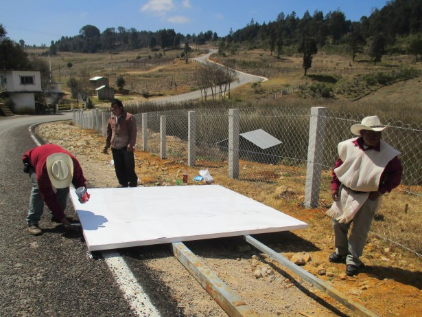 Candelaria residents paint over graffiti to fix up a roadside sign proclaiming their opposition to the highway project. (WNV/Sandra Cuffe)