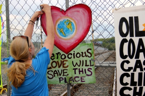 "A protester with the Break Free action in Albany tapes a piece of art that reads, ""ferocious love will save this planet,"" to a fence blocking entry to the Port of Albany. (WNV / William Fowler)"
