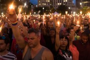 ORLANDO, FL - JUNE 13:  People hold candles during an evening memorial service for the victims of the Pulse Nightclub shootings, at the Dr. Phillips Center for the Performing Arts, June 13, 2016 in Orlando, Florida. The shooting at Pulse Nightclub, which killed 49 people and injured 53, is the worst mass-shooting event in American history. (Photo by Drew Angerer/Getty Images)