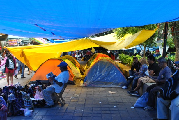 Teachers and souvenir sellers share the space below the canopies in the occupies main square of Oaxaca city. (WNV/Shirin Hess)