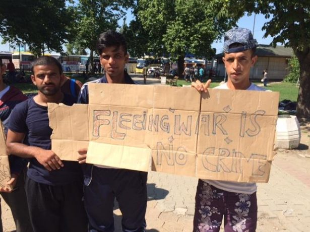 "Hunger striking refugees in Serbia hold a sign that reads ""Fleeing war is no crime"" while demonstrating near the border with Hungary. (Facebook / Refugee Aid Serbia)"