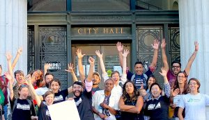 Advocates for worker cooperatives celebrate outside City Hall in Oakland after the city council passed a resolution supporting the development of democratic and equitable workplaces on September 8, 2015. (Sustainable Economies Law Center)