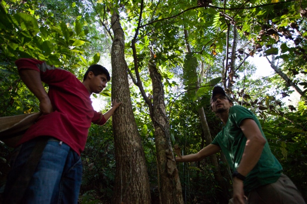David Bautista (left), a member of the La Bendición youth group, shares the community's water source with a small group of volunteers from the United States while Lucas Wolf from the organization Trees, Water, People, translates. (WNV/Jeff Abbott)