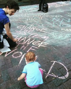 A child helps draw with chalk on the sidewalk during the march in Charlotte on September 24. (WNV / Roan)