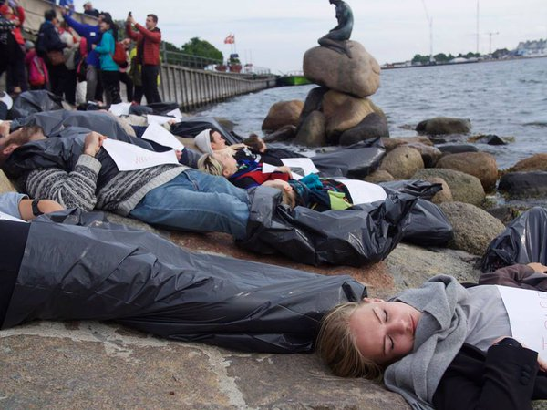 Danish activists stage a scene depicting a dead boat of refugees next to The Little Mermaid Statue in Copenhagen. (Twitter / @FlygtningeInfo)