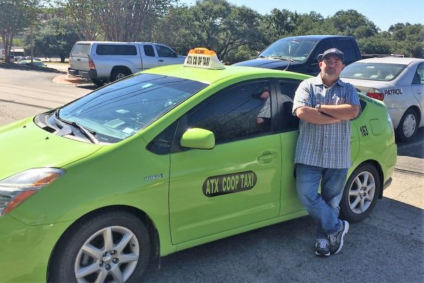 ATX Coop Taxi driver Ebrahim Elhadidi standing in front of his car. (WNV/Dave Passmore)