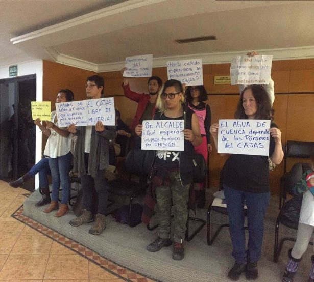 Yasunidos Cuenca-Guapondelig members holding protest banners after storming the City Council. (WNV/Yasunidos Cuenca)
