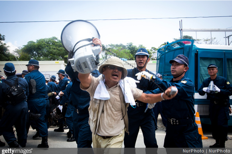 Anti U.S base leader Hiroji Yamashiro being removed by police after staging a sit-in protest protest against the construction of helipads in front of the gate of U.S. military's Northern Training Area in the village of Higashi, Okinawa Prefecture, on August 19, 2016. Japanese government resume construction of total six helipads in a fragile ten million year old Yanbaru forest that is home to endemic endangered species such as the Okinawan rail and Okinawan wood pecker. (Photo by Richard Atrero de Guzman/NURPhoto) (Photo by Richard Atrero de Guzman/NurPhoto via Getty Images)