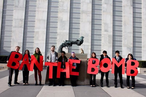 "People hold ""ban the bomb"" sign outside the United Nations headquaters"