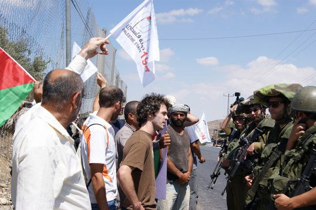 Protesters in Palestine face a row of Israeli soldiers.