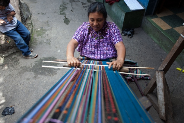 A woman weaves in Guatemala using a backstrap loom.