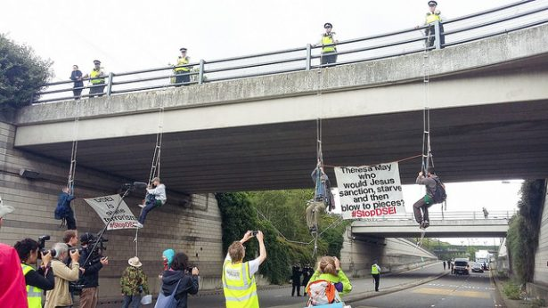 Activists rappel from bridge in DSEI protest.