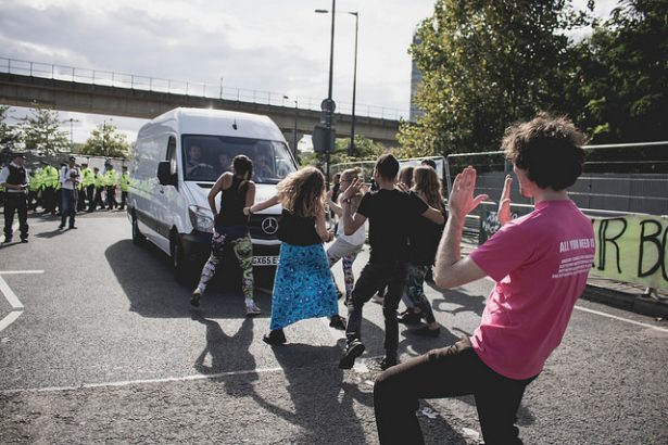 Dancers block vehicle in DSEI protest.
