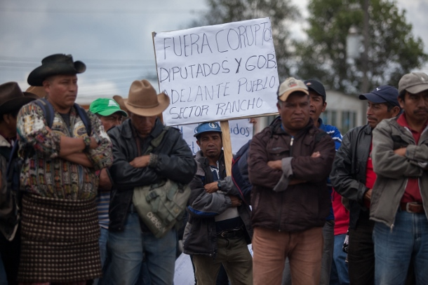 """A man with a sign that reads """"Out with the corrupt deputies and government. Forward with the people."""""""